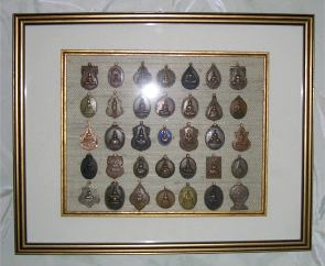 collection of small buddha medals - one of two framed sets