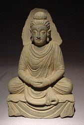 See a full page on this extraordinary Gray Ghandaran Schist seated Buddha (9in tall) - ca. 300 AD